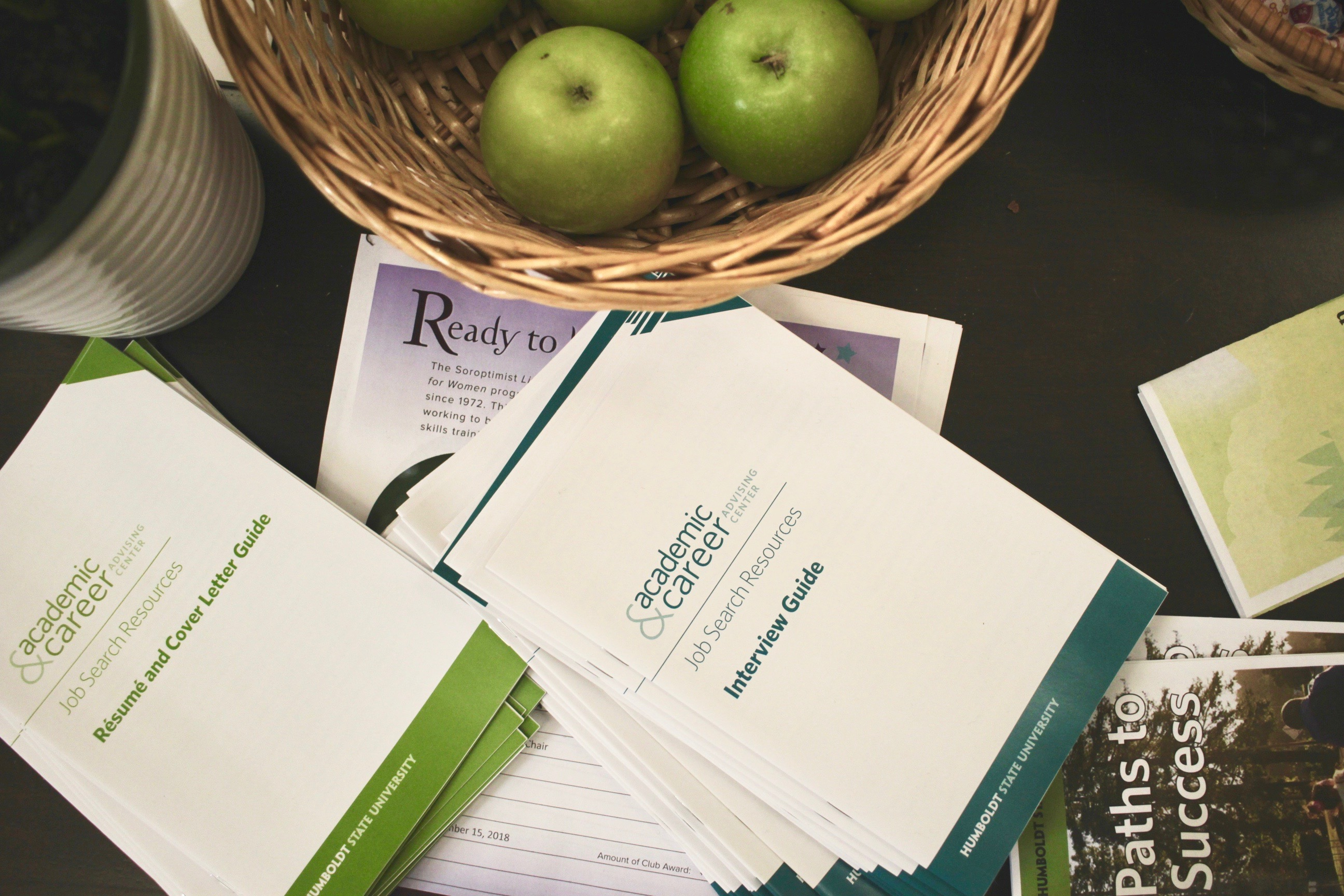 Flatlay photo of the front desk table with apples and our interview and resume booklets