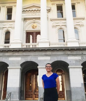 Katie wearing a blue shirt and black knee length skirt, in front of the state capital building.