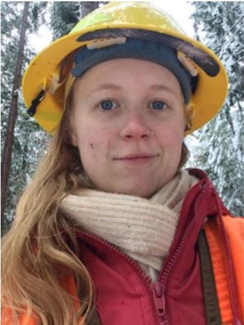 Sylvia Royen in the forest wearing a yellow hard hat, a beige scarf, red coat and an orange vest.